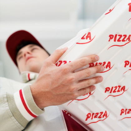 Pizza delivery man holding pizza boxes, low angle view, focus on boxes