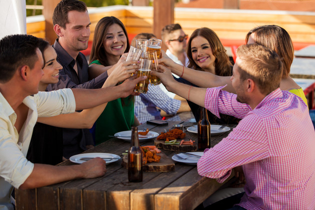 Large group of friends having fun and drinking beer at a restaurant